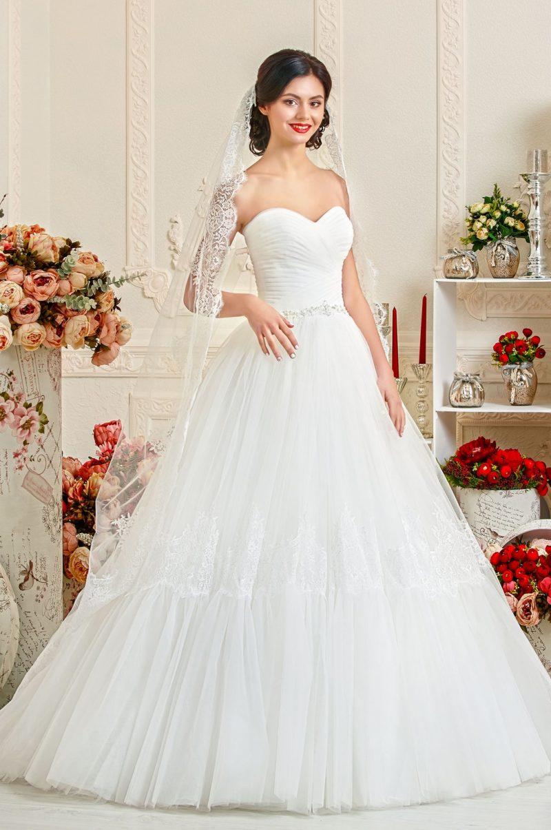 Открытое свадебное платье с драпировками на корсете и кружевным декором юбки.
