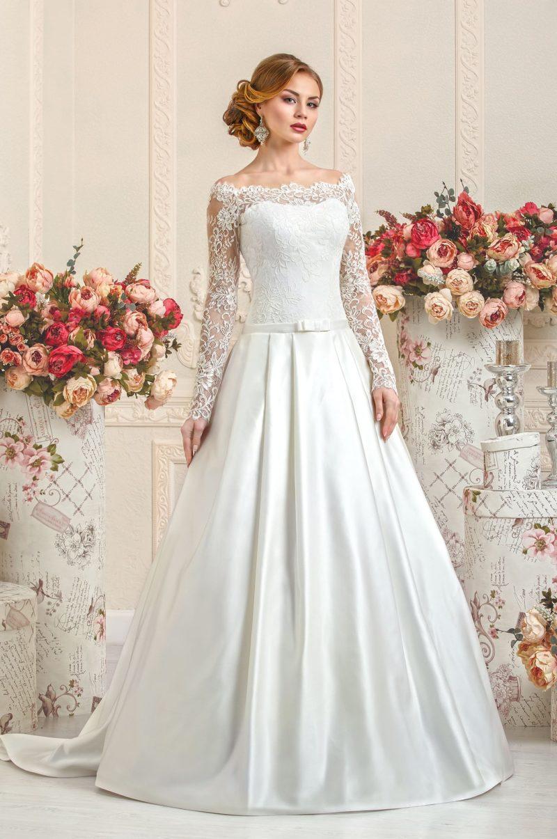 Атласное свадебное платье с длинными рукавами из кружева с крупным рисунком.