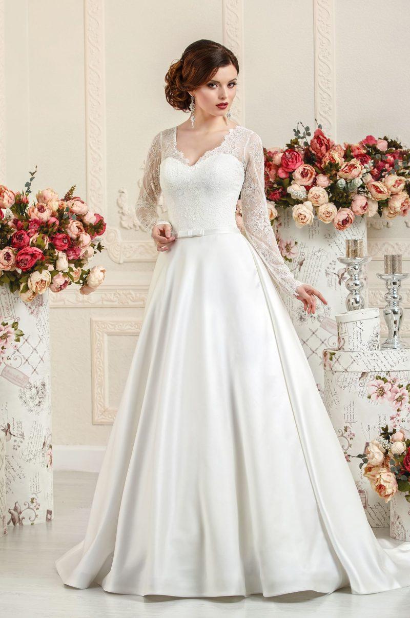 Закрытое свадебное платье с ажурными рукавами и атласной юбкой.