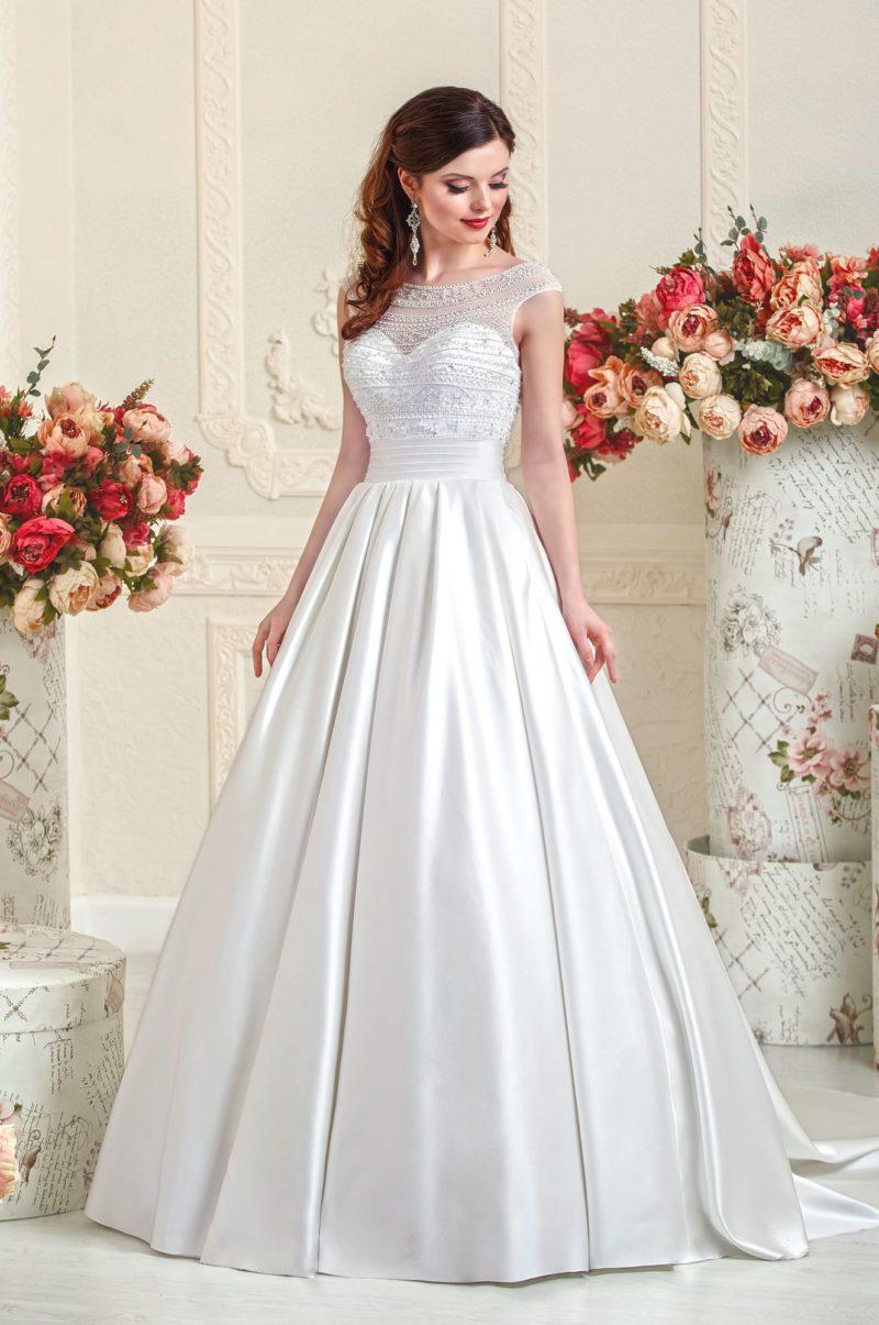 Атласное свадебное платье с полупрозрачной вставкой над корсетом.