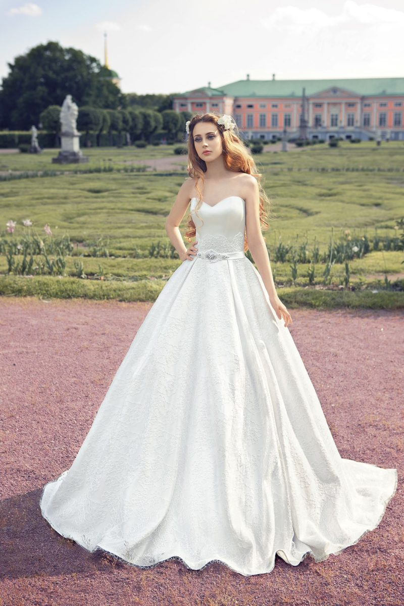 Открытое свадебное платье пышного силуэта с фактурной юбкой и широким поясом.