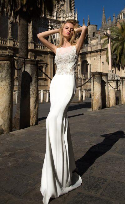 Закрытое свадебное платье прямого силуэта с небольшим шлейфом и фактурной вышивкой.