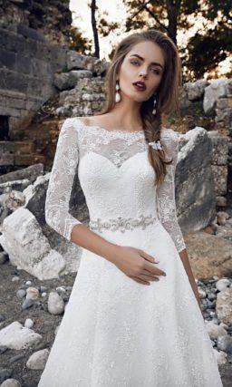 Свадебное платье силуэта «принцесса» с фигурным декольте и широким блестящим поясом.