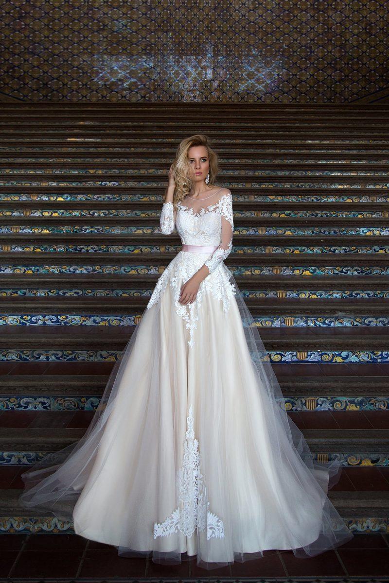 Пышное свадебное платье с многослойной юбкой и длинными кружевными рукавами.