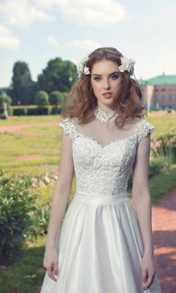 Пышное свадебное платье из атласной ткани с кружевной отделкой на открытом лифе.