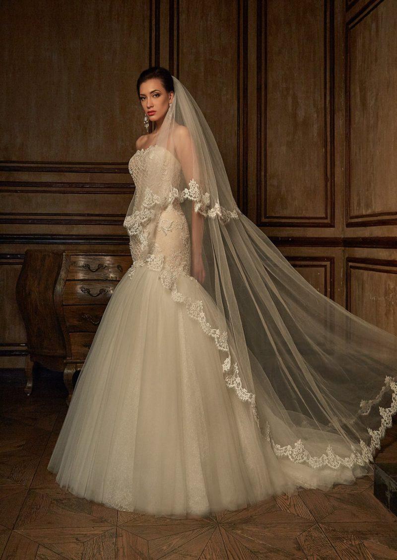Бежевое свадебное платье «русалка» с кружевной отделкой и пышным низом подола.