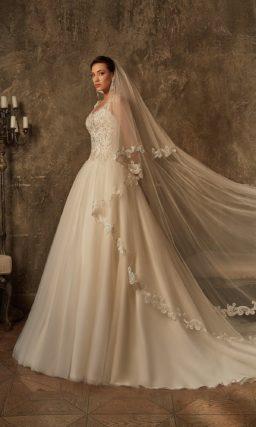 Торжественное свадебное платье с ажурным декором верха и многослойной пышной юбкой.