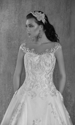 Пышное свадебное платье с длинным шлейфом, украшенное глянцевым кружевом с крупным рисунком.