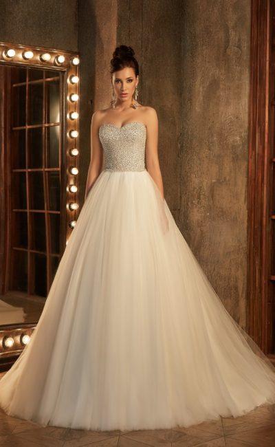 Впечатляющее свадебное платье бежевого цвета со сверкающим корсетом и юбкой А-силуэта.