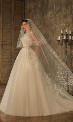 Пышное свадебное платье с длинным многослойным шлейфом и кружевной отделкой корсета.