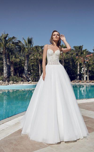 Пышное свадебное платье с многослойной юбкой и тонкими бретелями над открытым лифом.