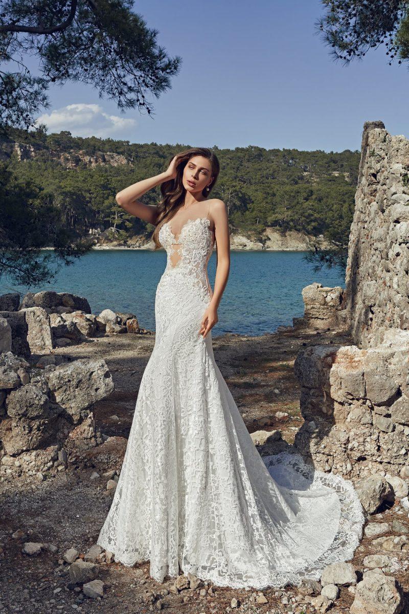 Свадебное платье с силуэтом «рыбка» и длинным шлейфом, дополненное глубоким декольте.