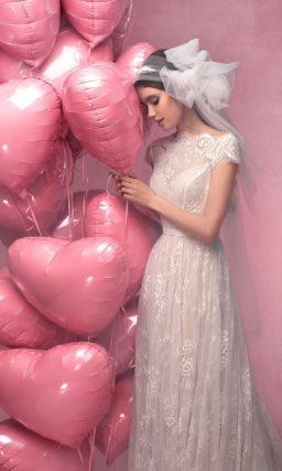 Закрытое свадебное платье прямого силуэта, выполненное из белого кружева на бежевой подкладке.