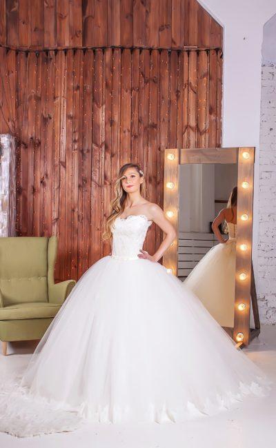 Невероятно объемное свадебное платье с романтичным открытым лифом, украшенным кружевом.