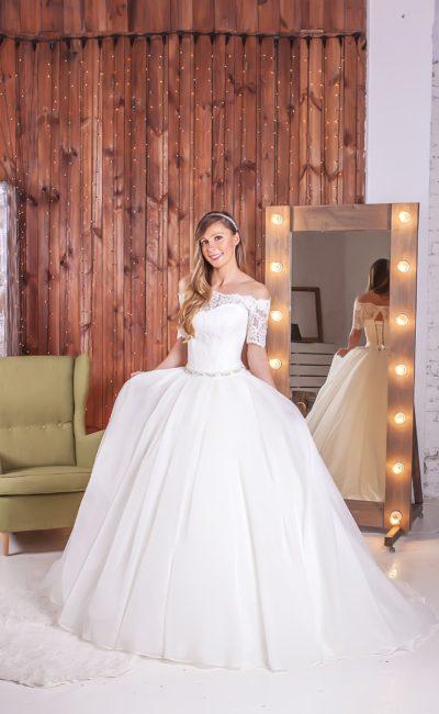 Великолепное свадебное платье с элегантным декольте, кружевным рукавом и пышной юбкой.