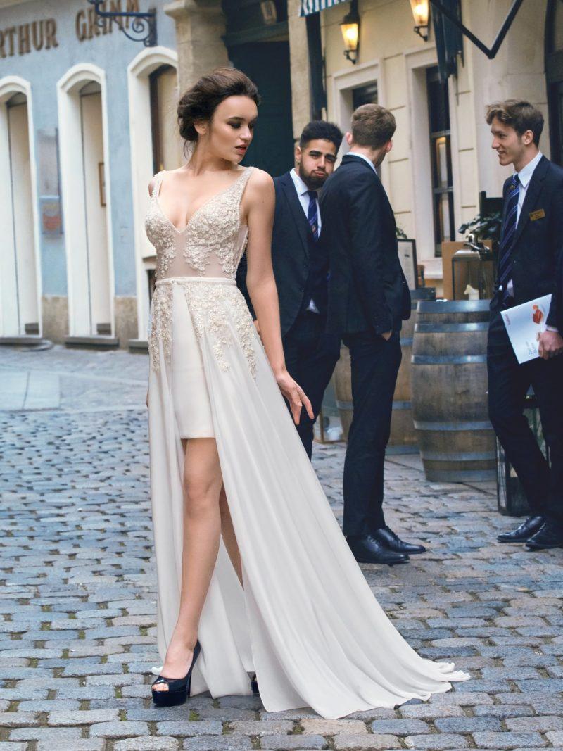 Прямое свадебное платье с короткой нижней юбкой и фактурными аппликациями отделки.