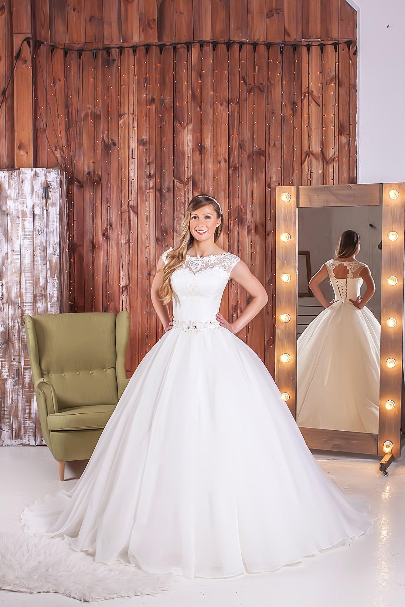Пышное свадебное платье с кружевной вставкой над лифом и вырезом «замочная скважина» сзади.