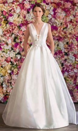 Свадебное платье А-силуэта, спинка которого оформлено кружевом, а лиф открыт глубоким декольте.