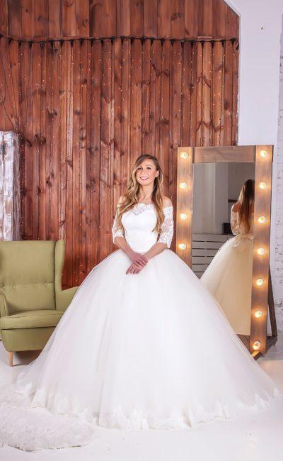 Роскошное свадебное платье пышного кроя со стильным портретным декольте и короткими рукавами.