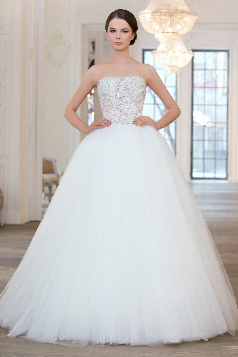 Торжественное свадебное платье с открытым лифом прямого кроя, украшенным кружевом.