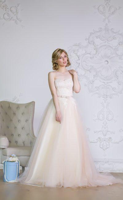 Свадебное платье с открытым кружевным корсетом и объемной юбкой кремового цвета.