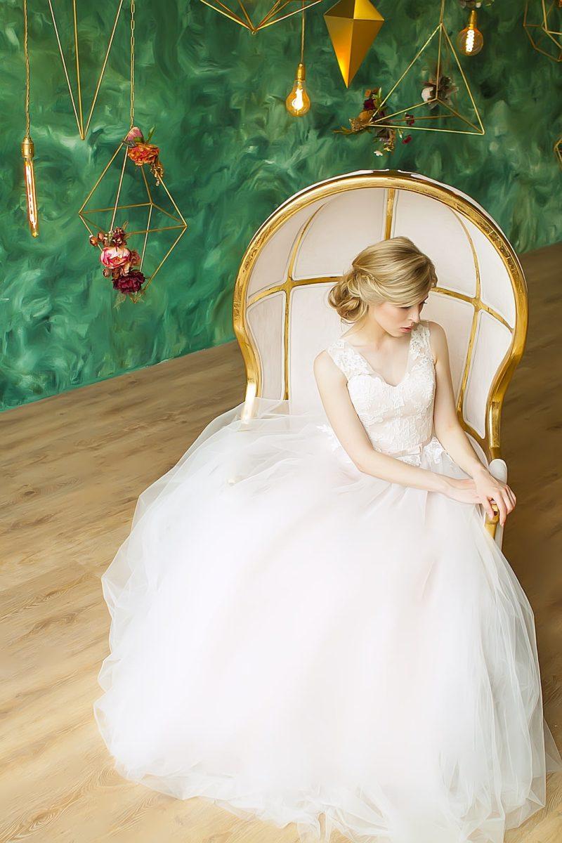 Пышное свадебное платье с элегантным бежевым корсетом, покрытым белой кружевной тканью.