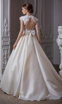 Атласное свадебное платье, открывающее декольте глубоким вырезом, с бантом на спинке.
