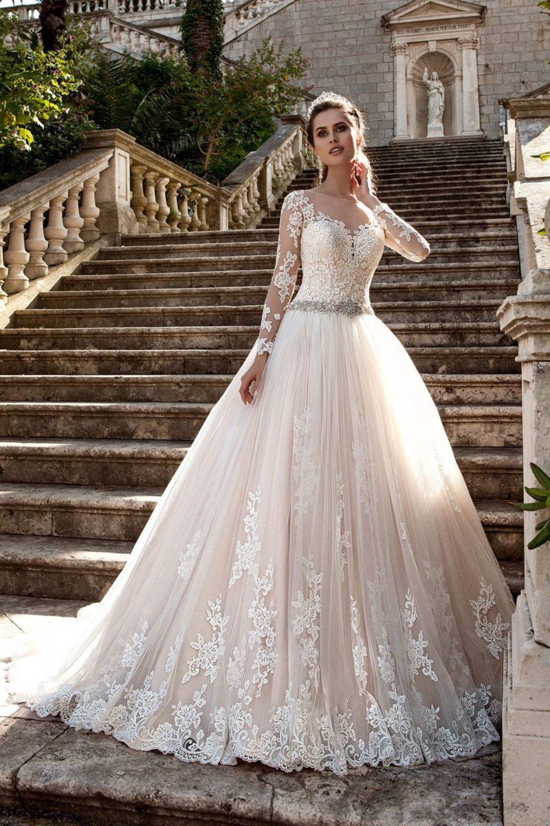 Пышное свадебное платье изысканного бежевого цвета с длинными полупрозрачными рукавами.