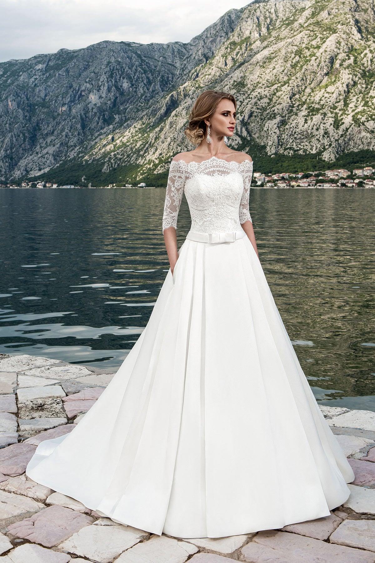 Свадебное платье А-силуэта с узким поясом на талии и кружевной отделкой верха с фигурным вырезом.
