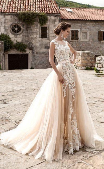 Бежевое свадебное платье облегающего кроя с верхней юбкой из нескольких слоев тонкой ткани.