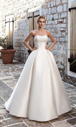 Атласное свадебное платье со складками по подолу и открытым корсетом с вышивкой на лифе.