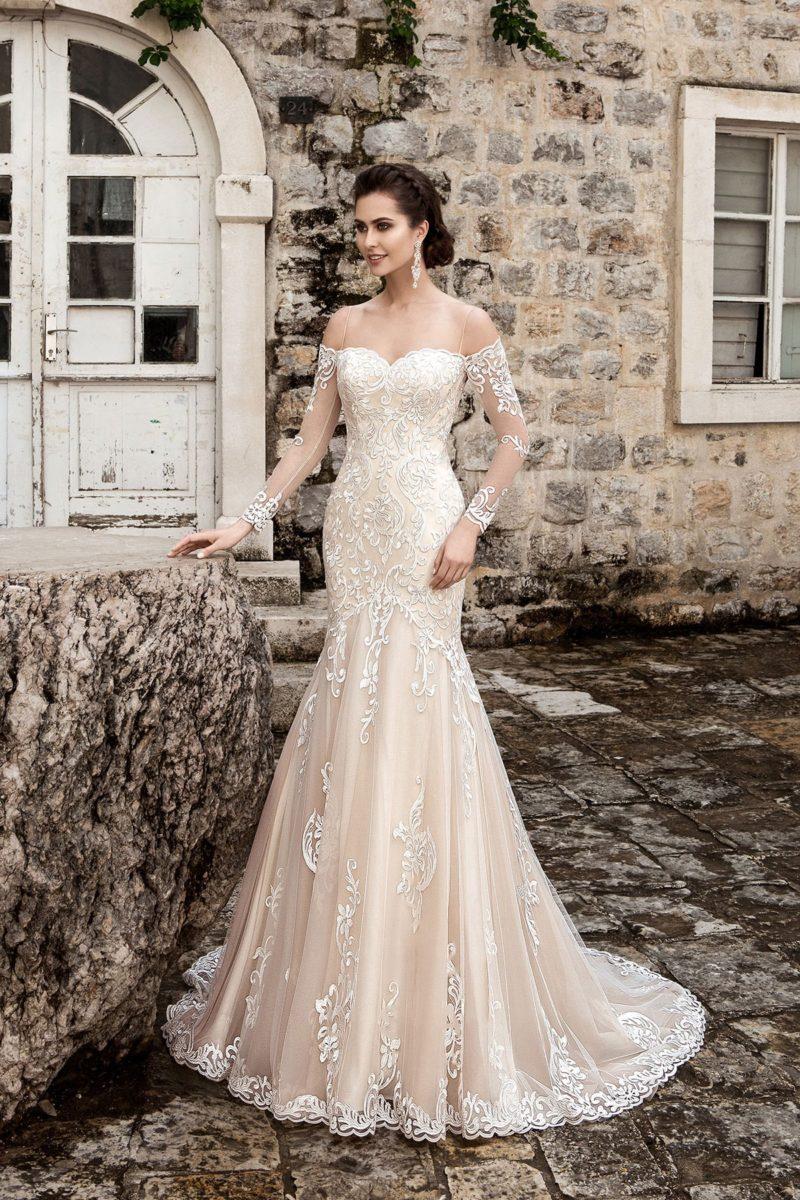 Кремовое свадебное платье с портретным декольте и длинными кружевными рукавами.