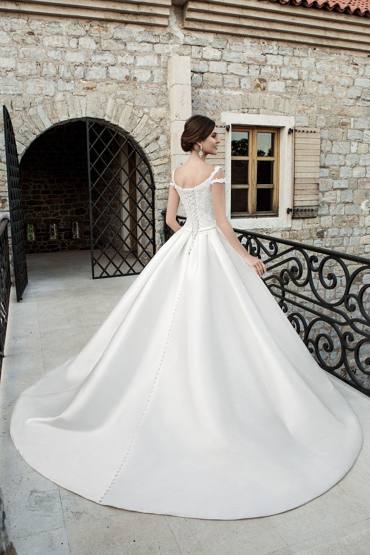 Свадебное платье с открытым декольте с кружевным декором и лаконичной юбкой со шлейфом.