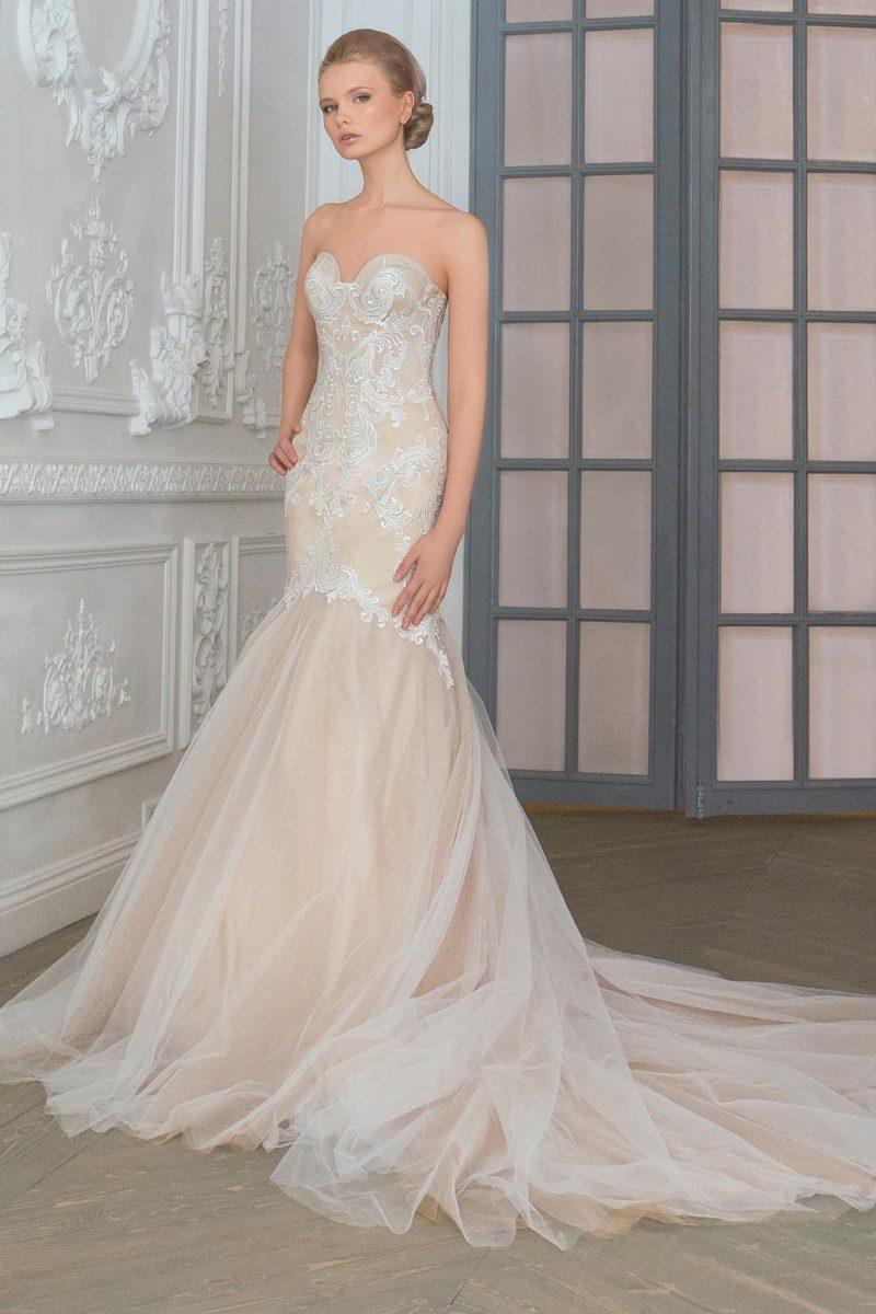 Кружевное свадебное платье облегающего кроя с бежевой подкладкой и многослойной юбкой.