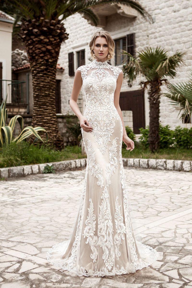 Облегающее свадебное платье на бежевой подкладке, покрытое крупными кружевными аппликациями.