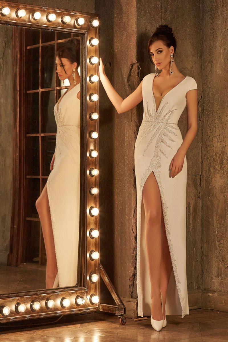 Прямое свадебное платье из атласной ткани, с глубоким декольте и разрезом на юбке.