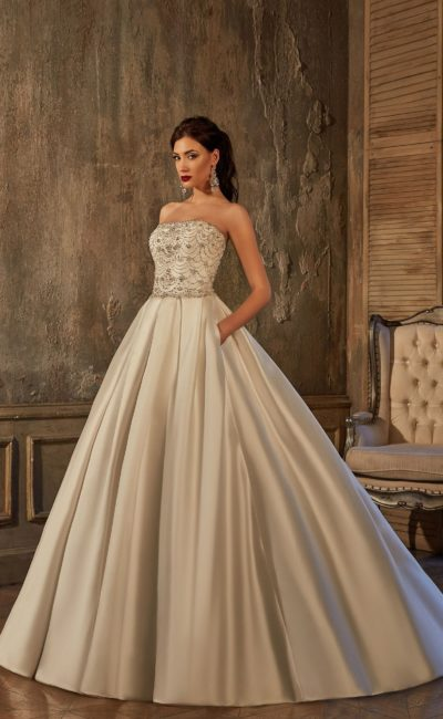 Пышное свадебное платье из атласной ткани, декорированное сияющей вышивкой.
