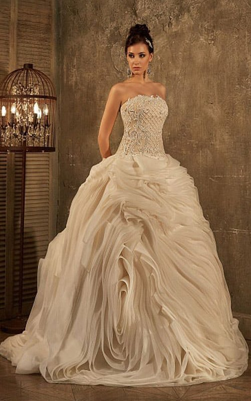 Драматичное свадебное платье с открытым верхом и юбкой, образованной пышными оборками.