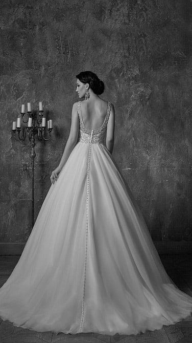 Сверкающее вышивкой свадебное платье с V-образным вырезом и пышным шлейфом.
