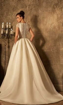 Закрытое свадебное платье с кружевной вставкой на спинке и объемной юбкой со шлейфом.