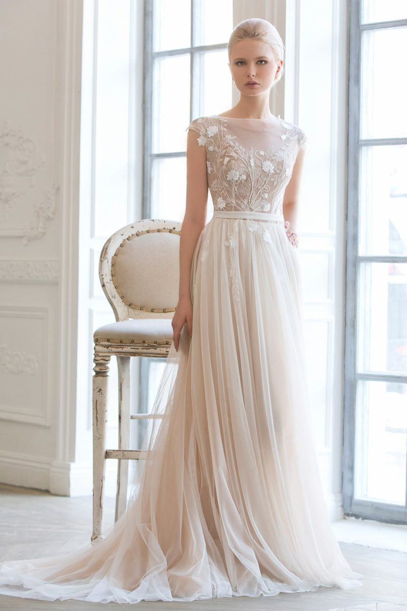 Свадебное платье цвета слоновой кости, с закрытым лифом и многослойной прямой юбкой.