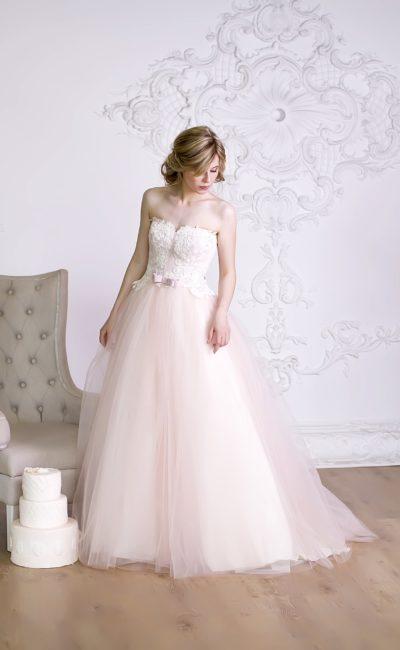 Романтичное свадебное платье с женственным верхом и многослойной розовой юбкой.