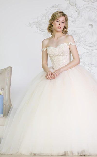 Свадебное платье цвета слоновой кости с чувственным декольте и объемным подолом.