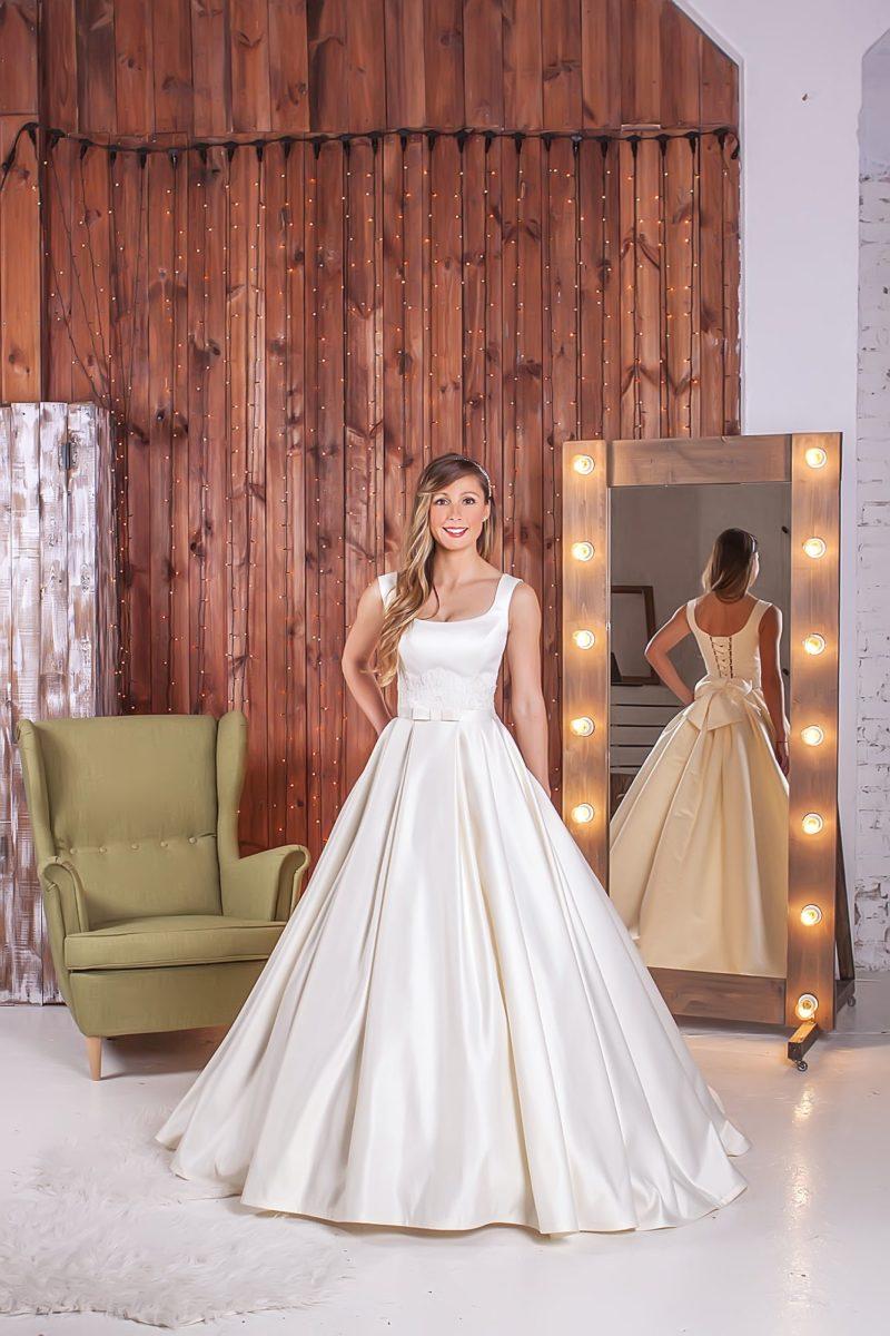 Элегантное свадебное платье «трапеция» из атласной ткани, украшенное сзади пышным бантом.