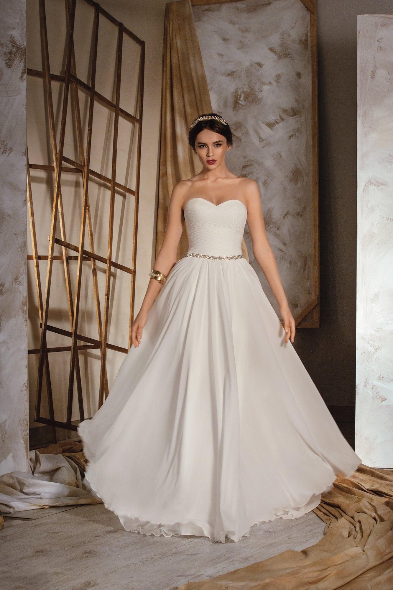 Лаконичное свадебное платье с открытым корсетом и многослойной юбкой, дополненное узким поясом.