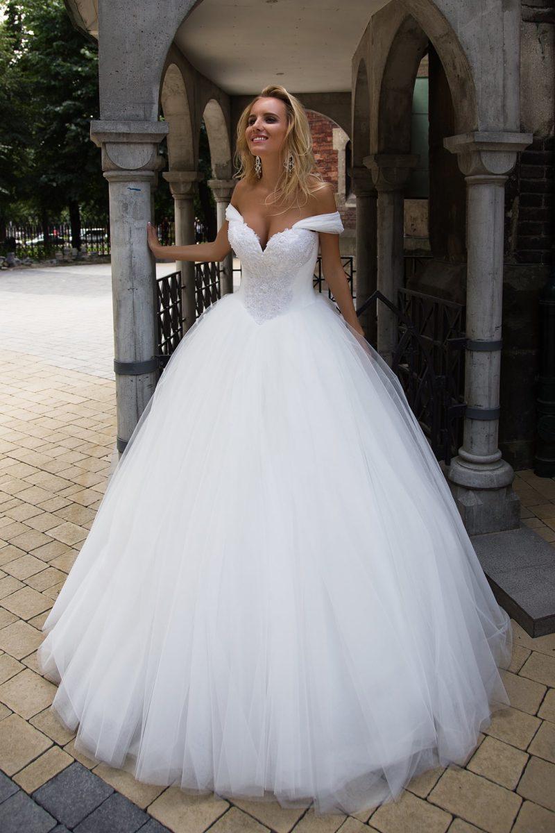 Женственное свадебное платье с потрясающим глубоким декольте и бретелями на предплечьях.