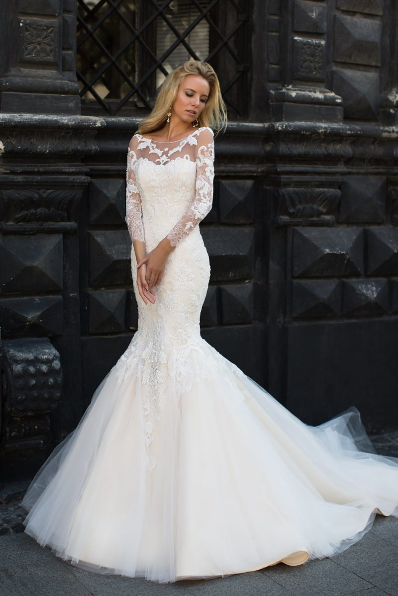 Кремовое свадебное платье «русалка» с длинными рукавами и изящным округлым вырезом.
