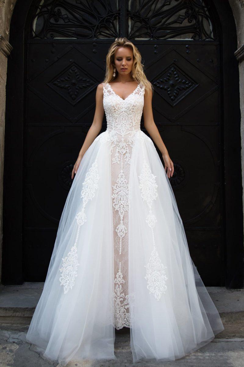 Свадебное платье с бежевой подкладкой, покрытой тонким кружевом, и пышной верхней юбкой.