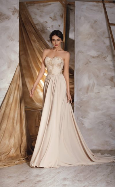 Прямое свадебное платье с открытым корсетом и юбкой со шлейфом, выполненное в кремовых тонах.