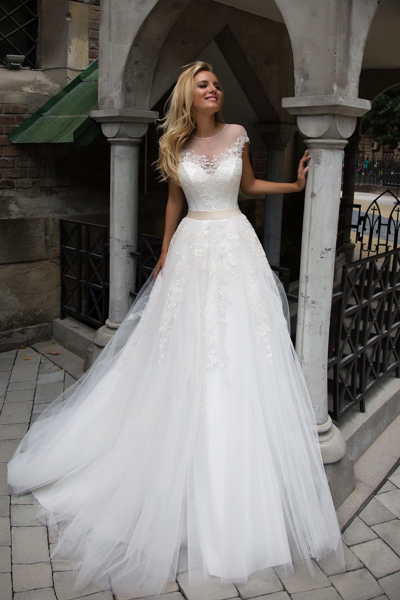 Женственное свадебное платье с кружевным декором верха и широким поясом кремового цвета.